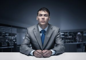Nervous man sitting at interview table.
